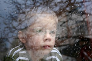 Photo - boy looking out window, rainy day